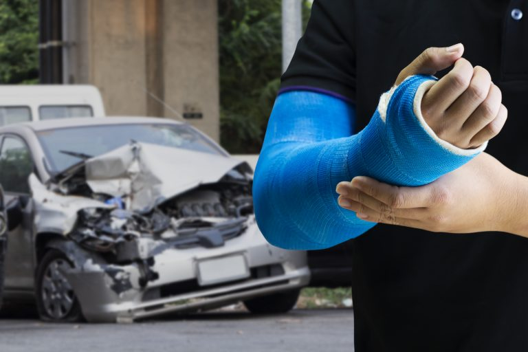 Man holding hand with blue bandage as arm injury with car accident